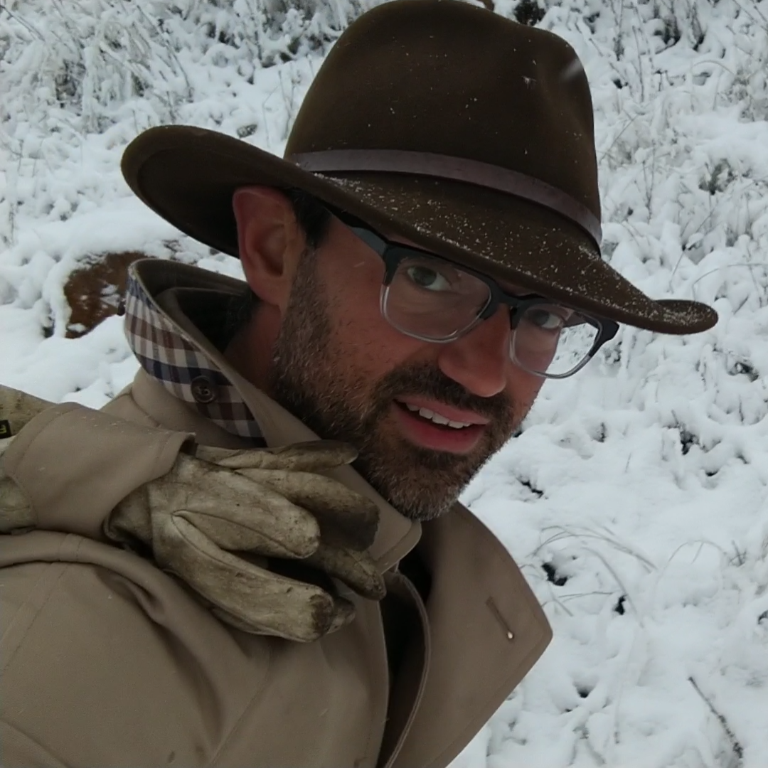 Ash Jackson man in hat and trenchcoat in snow